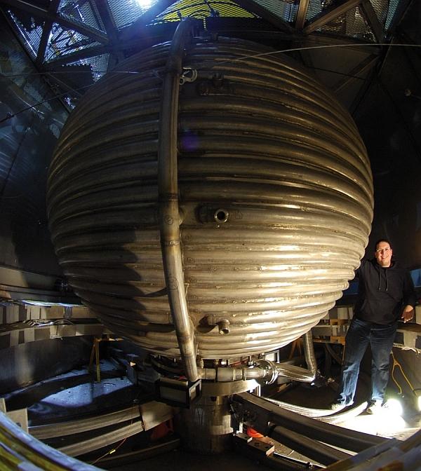 Один из создателей модели Земли рядом с конструкцией
