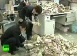 Сотрудницы китайского банка считают мелкие купюры, принесённые местным бизнесменом. Кадр RT