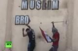 """Активисты сбивают табличку """"Братья-мусульмане"""" с одного из бывших офисов партии. Кадр RT"""